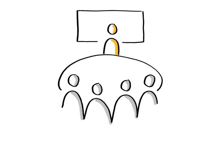 Vierergruppe an einem Tisch bei einer Präsentation