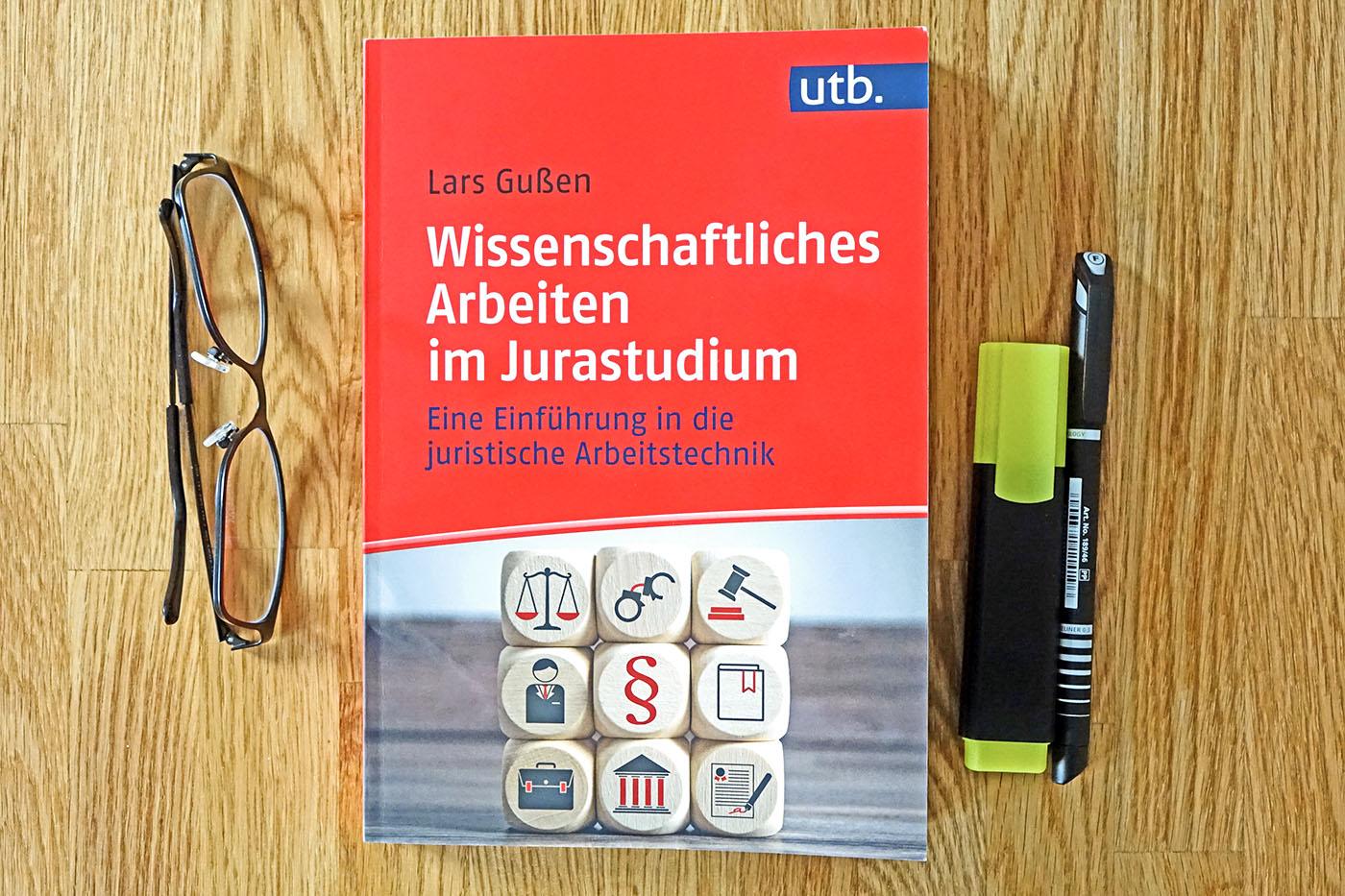 Buch wissenschaftliches Arbeiten im Jurastudium liegt auf dem Tisch, daneben eine Brille und zwei Stifte